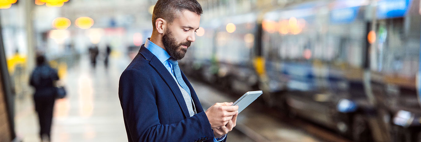 Business man looking at tablet at a train station.