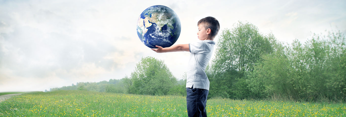 Boy holding Earth in a grassy field.
